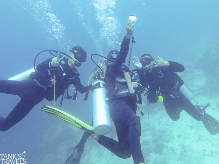 Divemaster trainees and their divemaster buddy taking underwater selfies. Shameful.